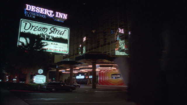 vidéos et rushes de ws view of illuminated hotel building with sign and cars pulling up at night - palace