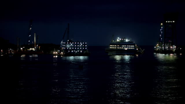 ws view of illuminated salvage operation platforms and upright costa concordia at night / giglio porto, tuscany, italy - passagierschiff stock-videos und b-roll-filmmaterial
