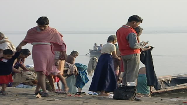 view of indian families washing their clothes by the river hindus perform daily ritual ablutions and prayers on the ganges - barefoot stock videos & royalty-free footage