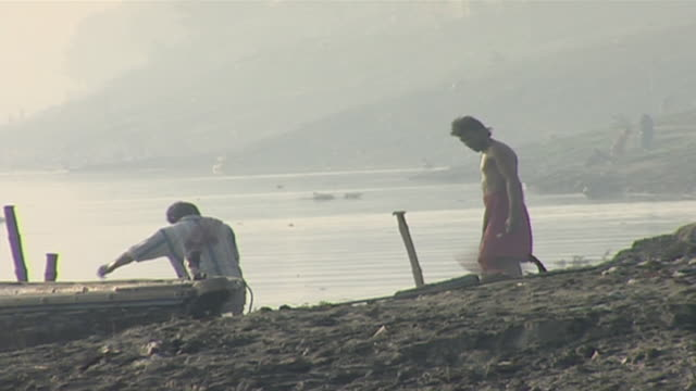 view of indian men performing ritual ablutions one is brushing his teeth on the embankment varanasi's ghats are integral to the hindu concept of... - barefoot stock videos & royalty-free footage