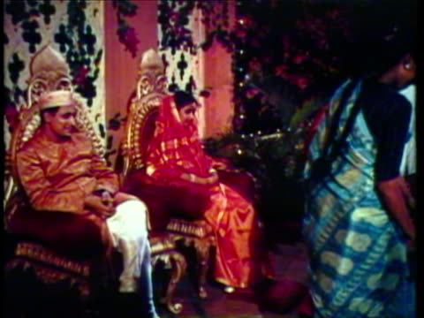 1953 ws ms view of indian wedding, bride and groom sitting on thrones while guests greet them, guests enjoy extravagant wedding feast / agra, new dehli, india / audio - agra stock videos and b-roll footage