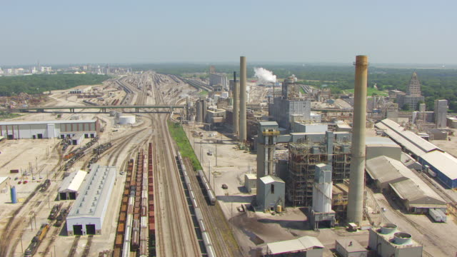 WS AERIAL POV View of industry with smoke stack and train yard / Decatur, Illinois, United States