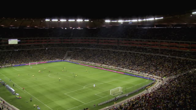 ws pan view of inside of soccer city during soccer match / johannesburg, gauteng, south africa - stadion stock-videos und b-roll-filmmaterial