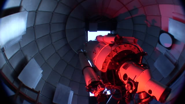 cu view of interior of telescope in reddish light as observatory dome turns above / kitt peak national observatory, arizona, usa - osservatorio video stock e b–roll