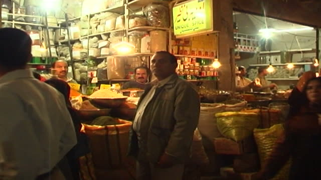 view of iranian shoppers passing a spice stall in one of the vaulted arcades of the bazaar in isfahan. - spice bazaar stock videos & royalty-free footage