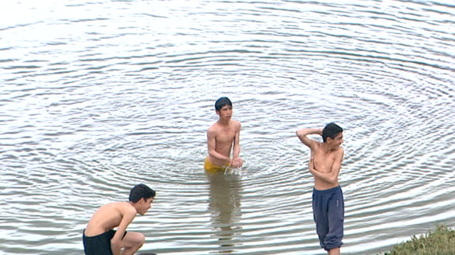 view of iraqi boys swimming near the bank of the shatt al-arab river. the river is formed by the confluence of the euphrates and tigris and runs into... - basra video stock e b–roll