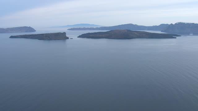 ws aerial view of island with ocaen / santorini, cyclades, greece - santorini stock videos & royalty-free footage