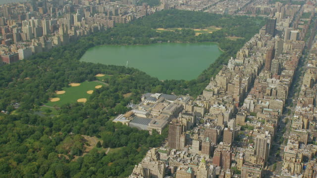 ws aerial view of jacqueline kennedy onassis reservoir and golf course in central park and roof of metropolitan museum of art / new york, united states - central park reservoir stock videos and b-roll footage