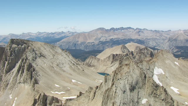 WS AERIAL POV view of Jagged Mountain Peaks and Mount Whitney surrounded by alpine lakes with Sierra Nevada and pine forests in the background / California, United States