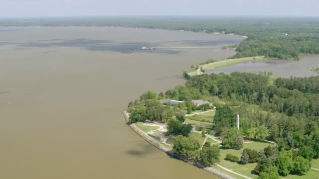 vídeos de stock e filmes b-roll de ws aerial pov view of jamestowne tercentennial monument at jamestown national historic site, river in background / jamestown, virginia, united states - jamestown virginia