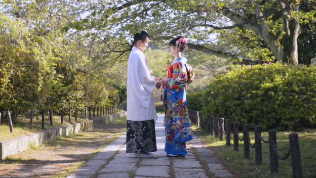 ws pan view of japanese couple in wedding kimonos / kyoto, japan - kimono stock videos & royalty-free footage