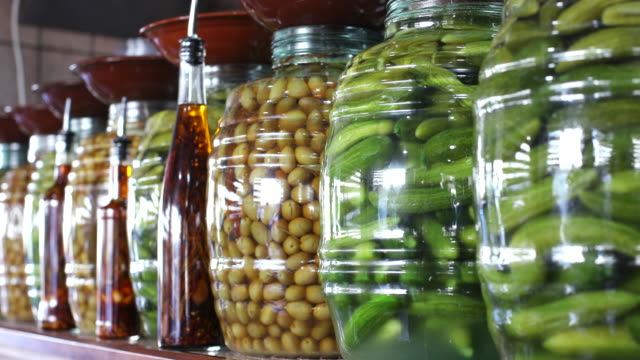 view of jars of pickled gherkins and olives and bottles of spiced vinegar and oil - vinegar stock videos & royalty-free footage