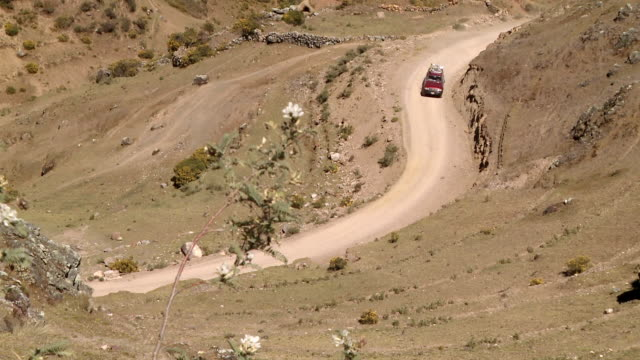 ws view of jeep driving along winding stony mountain road, from high vantage point at willkanuta mountain range, peru / cusco, peru - soil stock videos & royalty-free footage