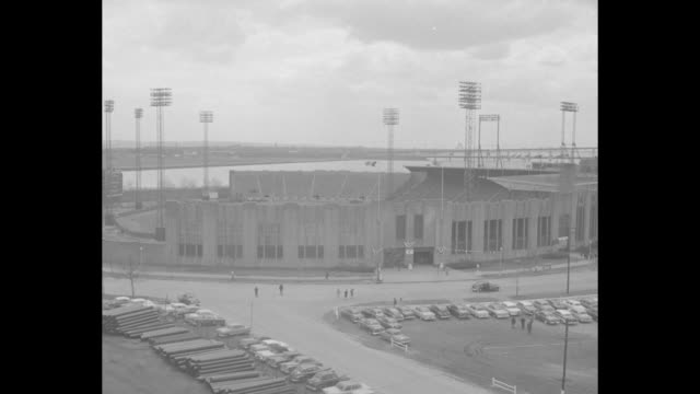 View of Jersey City with Manhattan skyline in bg / pan of Roosevelt Stadium exterior / people approaching stadium entrance / MS children getting off...