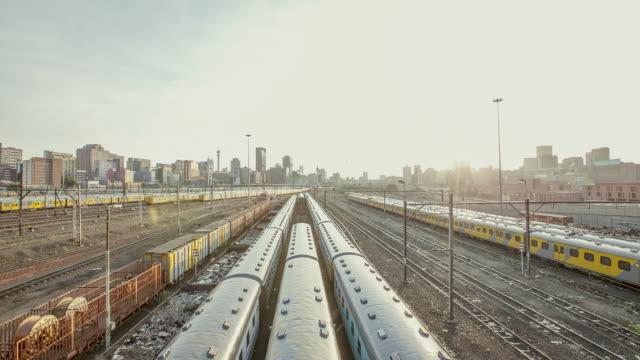 vídeos de stock e filmes b-roll de ws t/l view of johannesburg cityscape with train tracks / johannesburg, gauteng, south africa  - joanesburgo