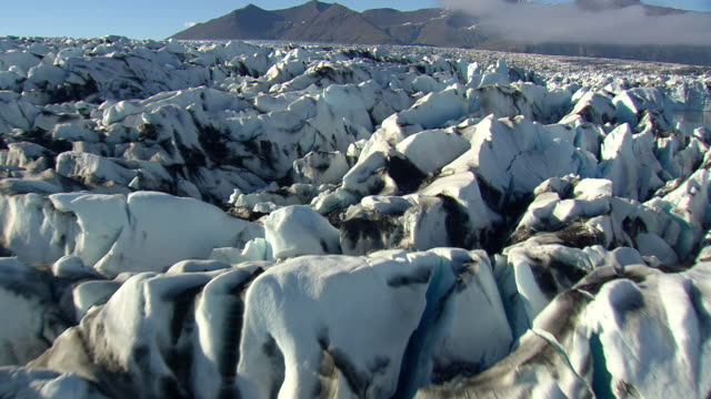 ws aerial zi view of jokulsarlon icebergs and glacier / iceland - jokulsarlon stock-videos und b-roll-filmmaterial