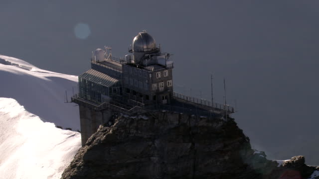 ms aerial ts zo view of jungfraujoch north face with hangiong glacier,sphinx observatory at top of saddle / jungfraujoch, bern, switzerland - berg jungfrau stock-videos und b-roll-filmmaterial