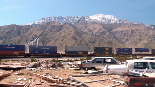 ws pan view of junkyard and cargo train passing with turbine farm and mountain in background / palm springs, california, usa - junkyard stock videos and b-roll footage