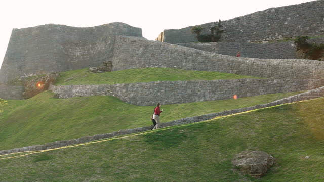ws pan view of katsuren castle and people walking / katsuren cho, okinawa, japan - 城点の映像素材/bロール
