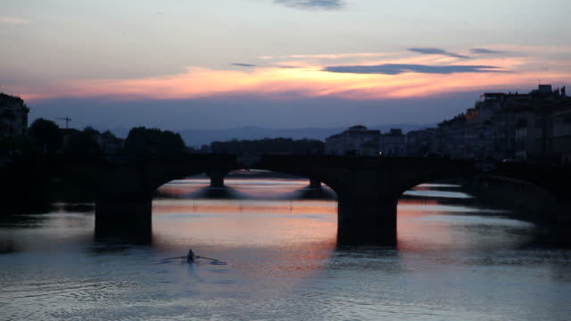WS View of kayaker rowing boat near river Arno at sunset / Florence, Italy