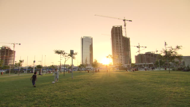 WS View of kids playing football on garden at sunset / Buenos Aires, Argentina