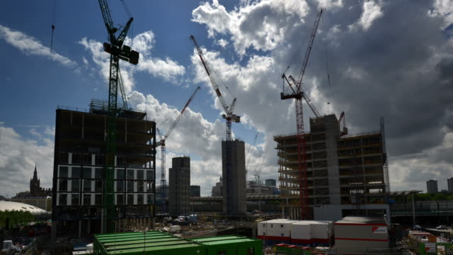 WS T/L View of Kings Cross construction tower Cranes working on early stage of office building construction billowing white and grey clouds on blue sky / London, Greater London, United Kingdom