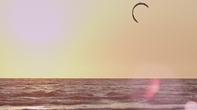 ws pan slo mo view of kite surfer surfing on sea at sunset / st. peter ording, schleswig holstein, germany  - deutsche nordseeregion stock-videos und b-roll-filmmaterial