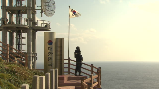 vidéos et rushes de view of korean soldier(dokdo guard) being on guard on the dokdo/takeshima island also known as liancourt rocks (natural monument heritage and one of most famous island in korea) in south korea - drapeau national