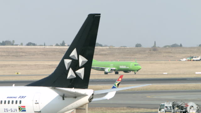 WS View of Kulula Airways 737-800 taxies from left with Star Alliance tail in front side / Johannesburg, Gauteng, South Africa / Johannesburg, Gauteng, South Africa