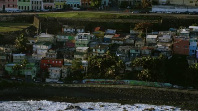 ws aerial pov view of la perla slum and colourful dwellings / la perla, old san juan, san juan, puerto rico, united states - スラム街点の映像素材/bロール