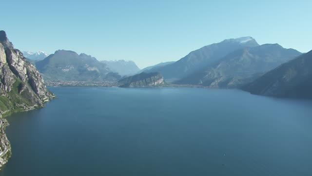 ws aerial view of lake and mountains in distance / lake garda, trentino, verona, brescia - トレンティーノ点の映像素材/bロール