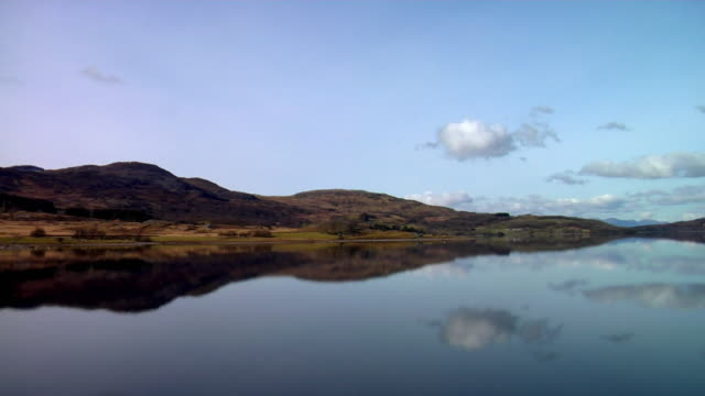 ws pan view of lake and mountains, nuclear power station in distance / trawsfynydd, snowdonia, uk - snowdonia video stock e b–roll