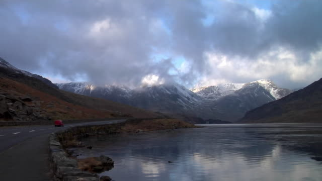 ws view of lake and snowcapped mountains with cloud, car passing by lake / capel curig, snowdonia, uk - snowdonia video stock e b–roll