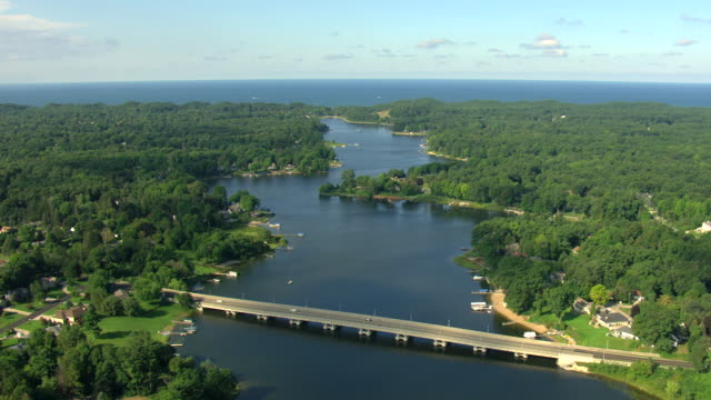 ws aerial view of lake michigan from mona lake with houses and boats on water in muskegon county / michigan, united state - michigan stock videos & royalty-free footage