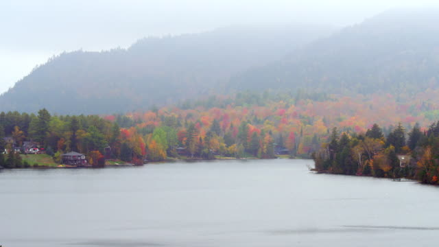 ws view of lake with haze covering foliage filled mountains / lake placid, new york, united states - lake placid town stock videos and b-roll footage