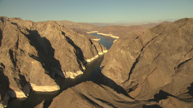 ws aerial view of lake with water history lines on surrounding rocky mountains with morning sunshine / lake mead, nevada, united states - sunshine lake bildbanksvideor och videomaterial från bakom kulisserna