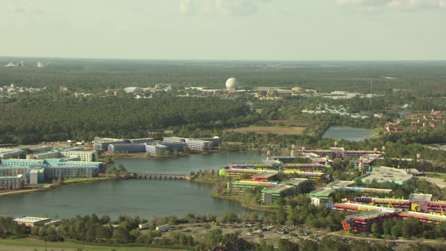 ws aerial view of landscape of disney world with epcot center and parking lots with bright signage on them in ground / orlando, florida, united states - epcot stock videos and b-roll footage