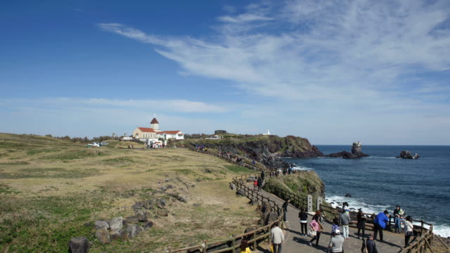 stockvideo's en b-roll-footage met ws t/l view of landscape of seopjikoji ( famous place for its scenics and drama set at jeju island ) coastal feature with tourists / seogwipo, jejudo, south korea - coastal feature