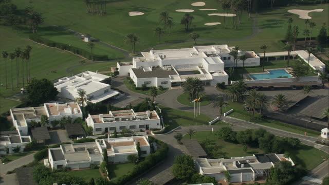 ws pov zo aerial view of landscape with golf course /  sotogrande, andalusia, spain - bandierina da golf video stock e b–roll