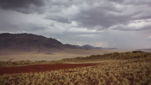 stockvideo's en b-roll-footage met ws t/l view of landscape with mountains, scrubby plain, earthy watering hole and boiling cloud formations with heavy rain / wolwedans, windhoek, namibia - namibië