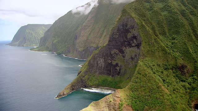 WS AERIAL View of large cliff surrounded by clouds on island of Molokai / Hawaii, United States