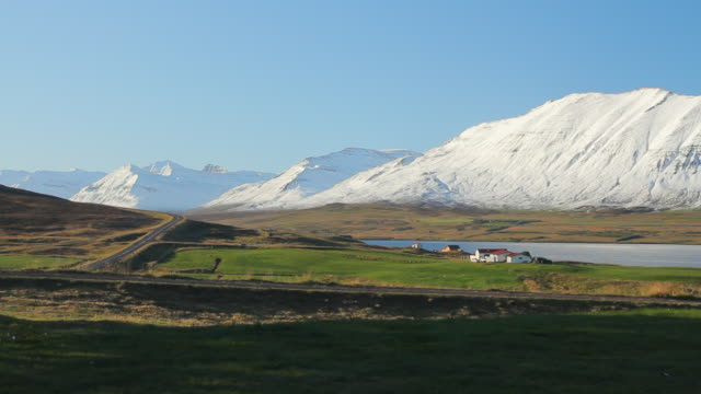 ws view of large field with small village, river water, and large mountains / skagafjorour, nordhurland vestra, iceland  - village点の映像素材/bロール