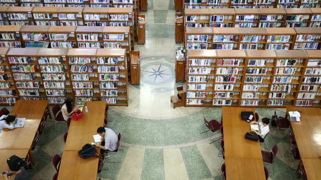 vidéos et rushes de view of large group of books and bookshelves at the library of kyunghee university - rayonnage de livre
