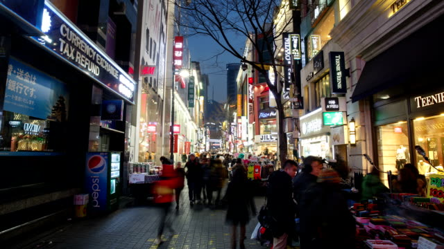 view of large group of people on the myeong dong street (tourist most visited places and one of the primary shopping districts in seoul) at night - south korea stock videos & royalty-free footage