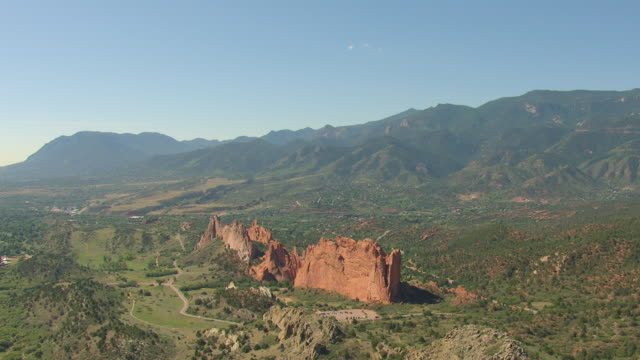 WS DS AERIAL View of large red rocks formations in valley in between mountain ranges in daylight / Colorado Springs, Colorado, United States