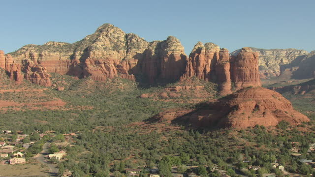 vídeos de stock e filmes b-roll de ws aerial view of large rock formations over town / sedona, arizona, united states  - arenito