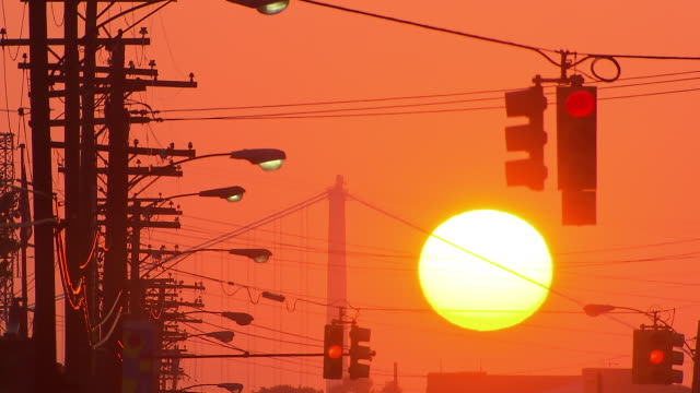 ws view of large yellow sun rising behind ambassador bridge, streetlights & telephone poles & traffic lights / detroit, michigan, united states - road signal stock videos & royalty-free footage