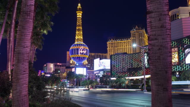WS T/L View of Las Vegas Replica Eiffel Tower with traffic moving in foreground / Las Vegas, Nevada, United States