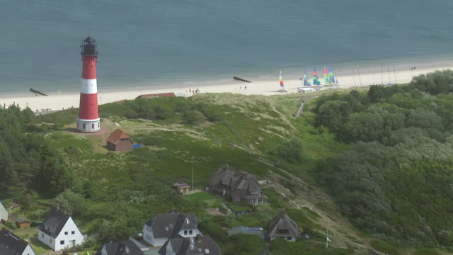 ws aerial zi ds view of light house along coast of sylt island in noth sea / sylt, schleswig holstein - north sea stock videos & royalty-free footage