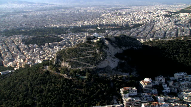 ws aerial zi view of likavitus cityscape and lycabettus mountain with saint george chapel on top. wide shot over athens /  likavitus, lycabettus, athens, greece - lycabettus hill stock videos & royalty-free footage